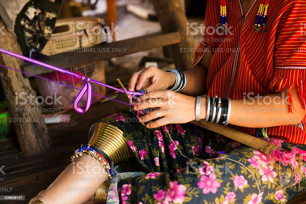 Hill Tribe Woman in Thailand Weaves on Wooden Porch stock photo