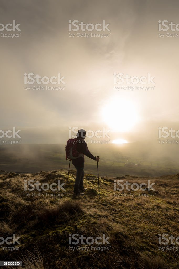 Hill walker looking at the sun over valley stock photo