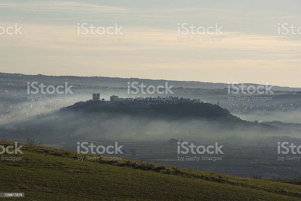 hill wrapped in fog stock photo