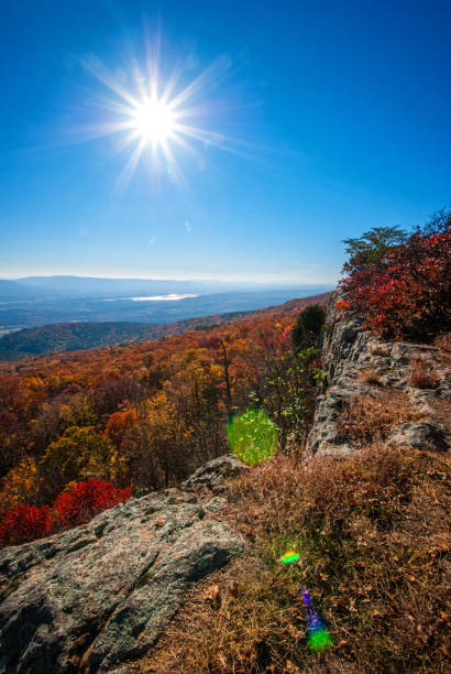 Hills Ablaze with Autumn Color View of vibrant fall colors with valleys,hills and lake in background. along with evening  sun and starburst. ablaze stock pictures, royalty-free photos & images
