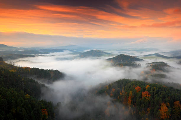Hills and villages with foggy morning. Morning fall valley of Bohemian Switzerland park. Hills with fog, landscape of Czech Republic, landscape from Ceske Svycarsko. Czech typical autumn landscape. stock photo