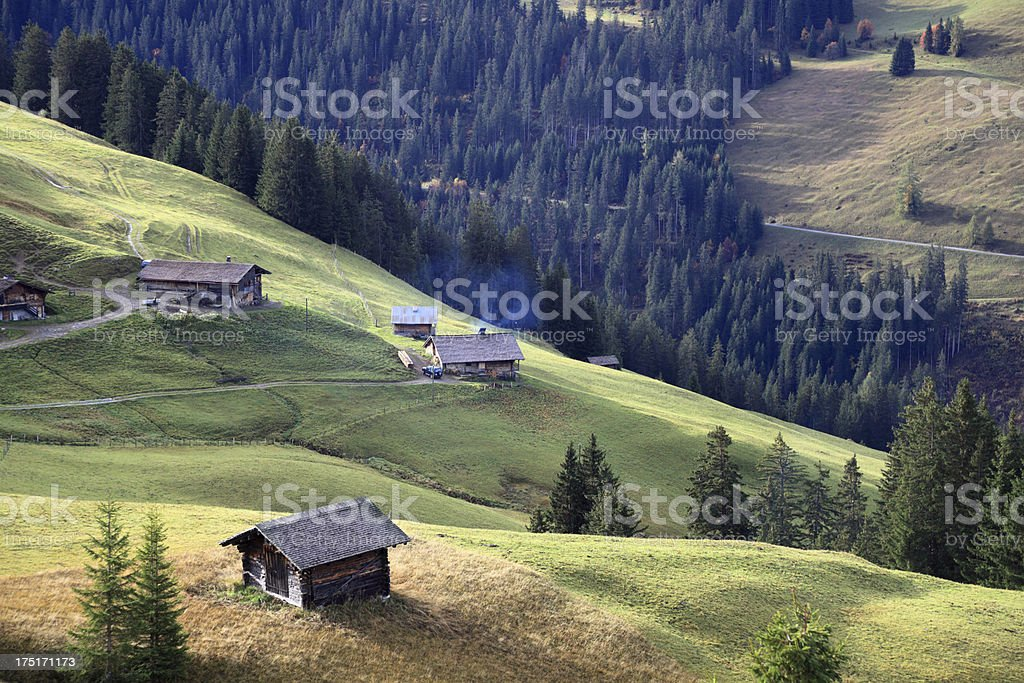 hills and wooden huts in sunny swiss alps royalty-free stock photo