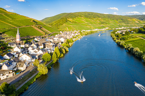 Hills with vineyards and church in Merl village of Zell (Mosel) town, Rhineland-Palatinate, Germany. Water skiing, barges, speedboats on the Moselle river meander