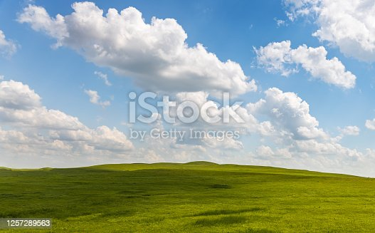 A beautiful cloudscape with blue sky and a rolling green hill.
