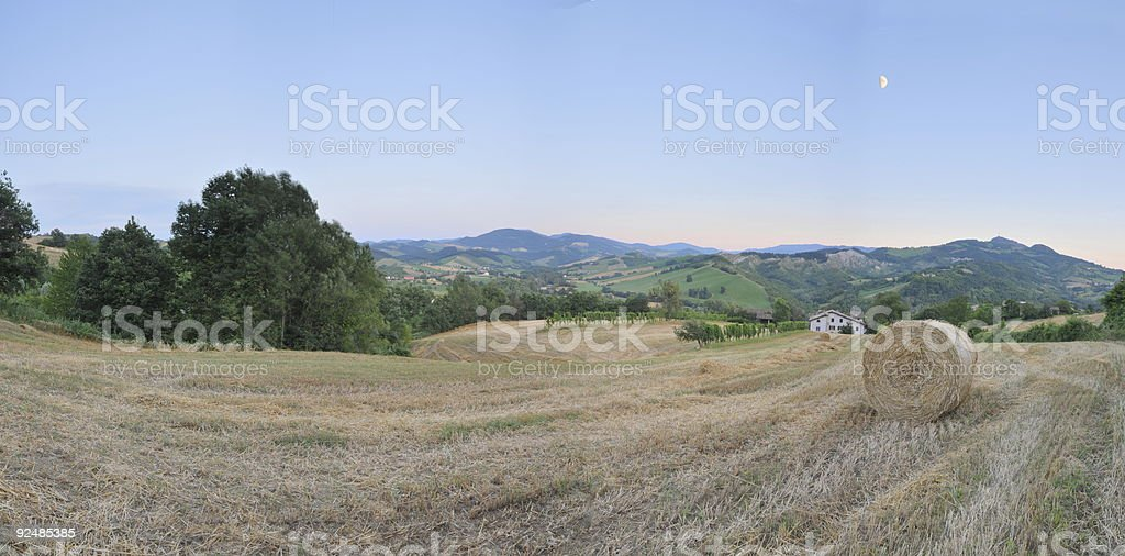 hillside country scene with straw bale, field and farm house royalty-free stock photo