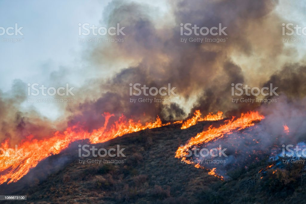 Hillside on Fire with Bright Flames and Black Smoke during California Woolsey Fire Hillside on fire with bright orange flames and black smoke making heart shape during California Woolsey Fire Burning Stock Photo