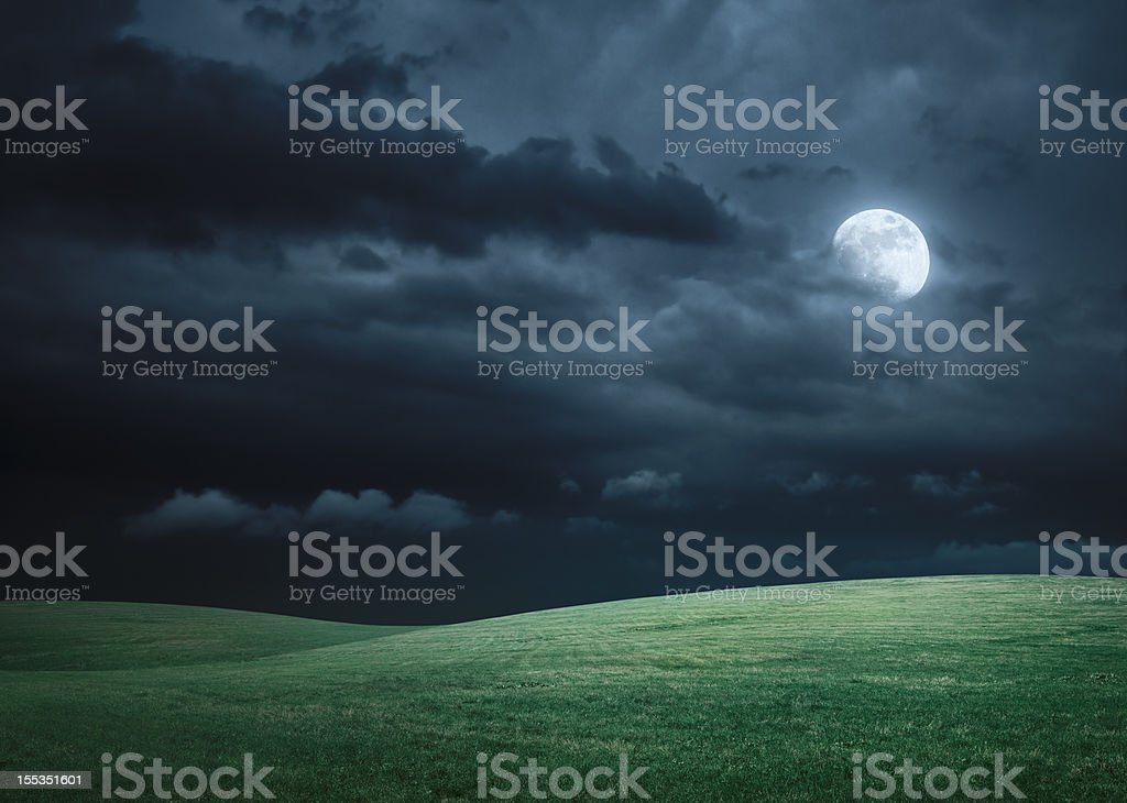 Hilly meadow at night with full moon, clouds and grass stock photo