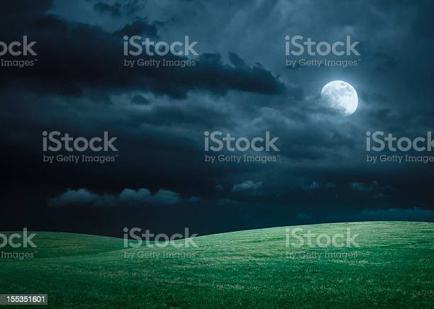 Photo of Hilly meadow at night with full moon, clouds and grass