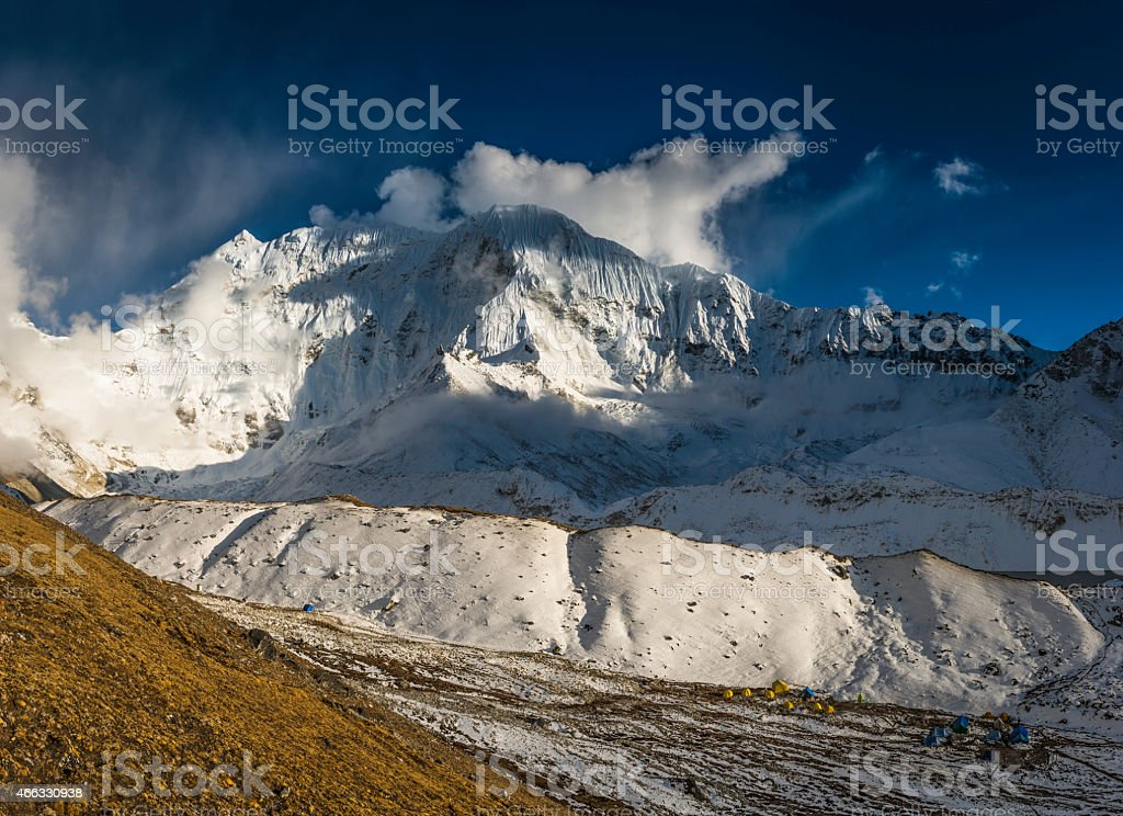 Himalaya expedition basecamp snowy mountain peaks dramatic cloud light Nepal stock photo