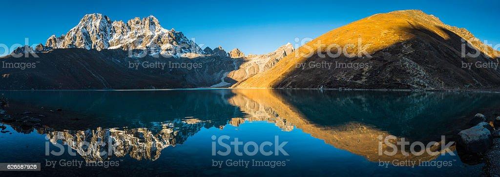 Himalaya mountain peaks reflecting in tranquil Gokyo Lake panorama Nepal stock photo