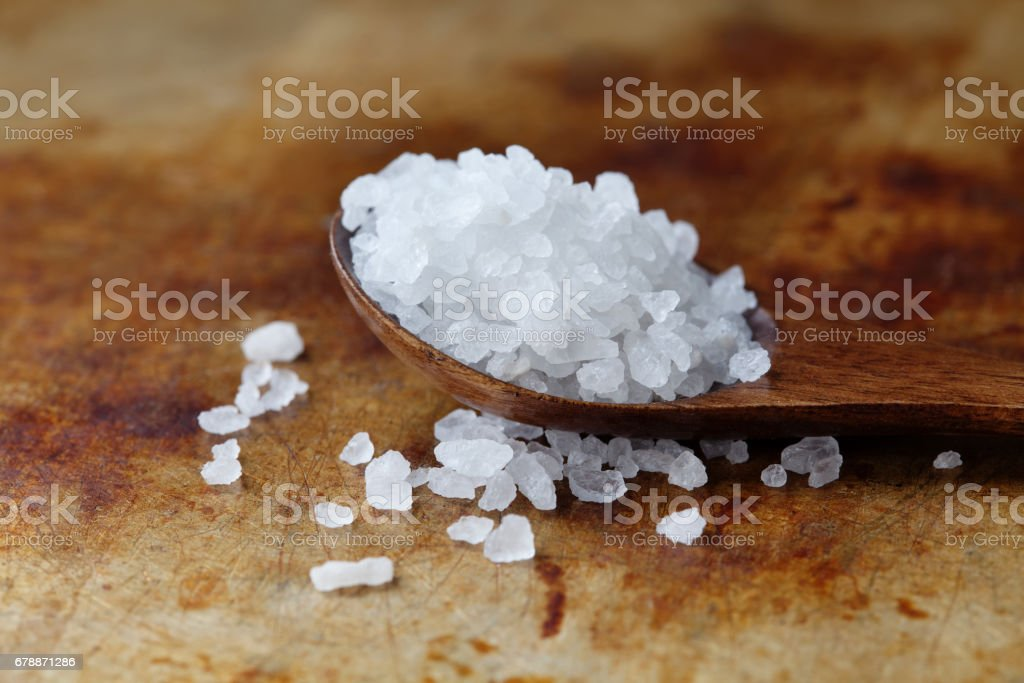 Himalayan Halite salt condiment macro view. Natural mineral flavoring food preservative, Saline sodium chloride white crystal in wooden spoon, aged rusty background. Shallow depth field stock photo