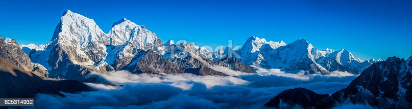Deep blue high altitude skies above the snowy summits of Cholatse (6440m), Taboche (6542m), Kangtega (6752m) and Thamserku (6623m) rising through the clouds covering the Ngozumpa glacier and Gokyo deep in the remote Himalayan mountain wilderness of the Everest National Park on the Nepal Tibet border, a UNESCO World Heritage Site.