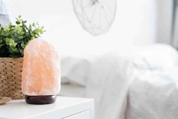 lámpara himalayan de la rosa cristales de sal sobre la mesa en el dormitorio, terapia saludable. - salado fotografías e imágenes de stock