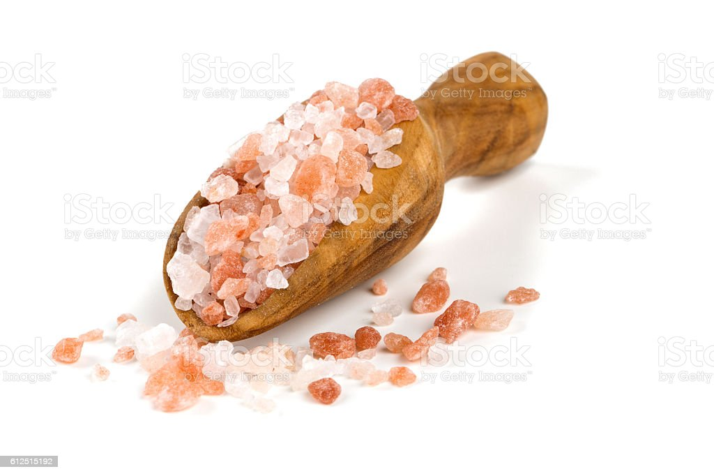 himalayan salt on a wooden spoon over white stock photo
