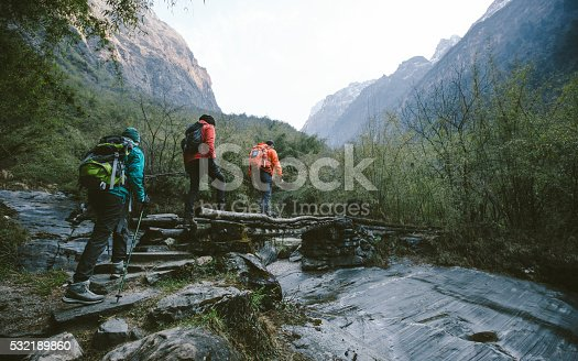 Group of trekkers cross the bridge at Annapurna region on Himalayas.