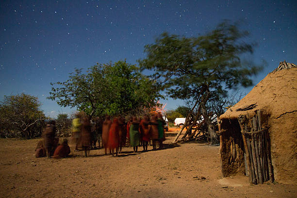 Himba People By The Mud Hut At Night stock photo
