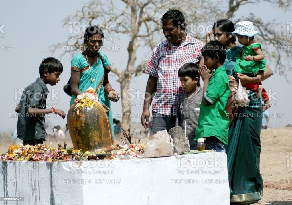 Hindu devotees perform puja to lord siva idol scupted out of stone on maha siva ratri day stock photo