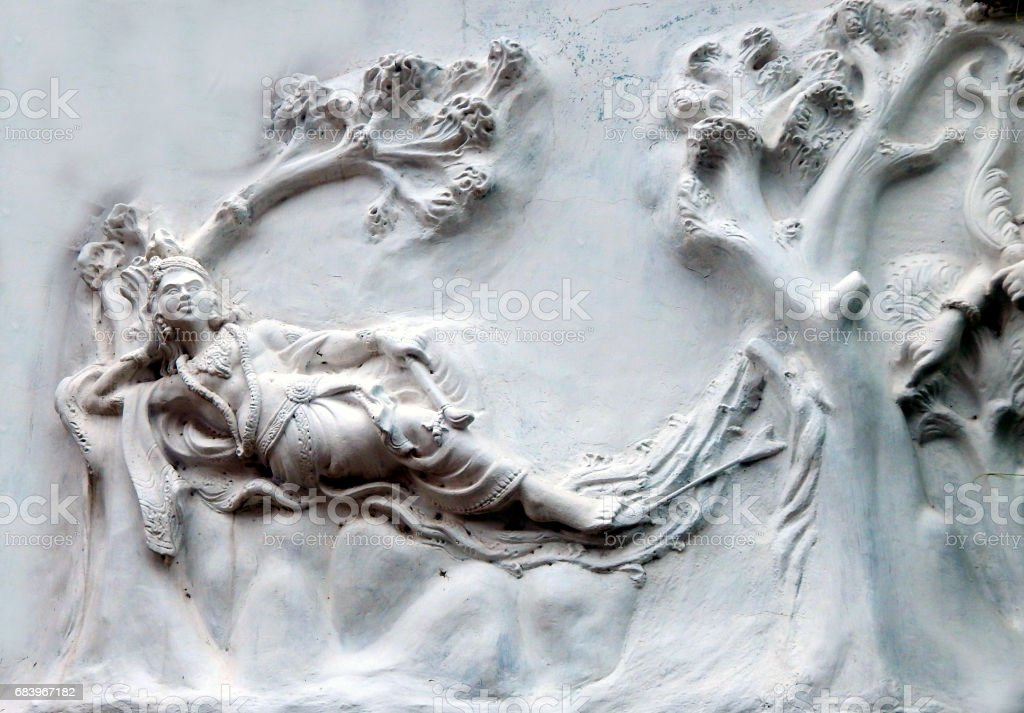 Hindu god sri krishna taking rest on exterior wall of temple as in epic Mahabharata,India stock photo