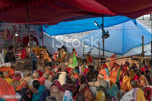 Hindu guru giving a lecture to a small crowd of followers, under a tent, during afternoon. Photo taken during Kumbh Mela 2019 in Prayagraj (Allahabad), India.  Kumbh Mela or Kumbha Mela is a major pilgrimage and festival in Hinduism, and probably the greatest religious festival in the World. It is celebrated in a cycle of approximately 12 years at four river-bank pilgrimage sites: the Allahabad (Ganges-Yamuna Sarasvati rivers confluence), Haridwar (Ganges), Nashik (Godavari), and Ujjain (Shipra). The festival is marked by a ritual dip in the waters, but it is also a celebration of community commerce with numerous fairs, education, religious discourses by saints, mass feedings of monks or the poor, and entertainment spectacles. Pilgrims believe that bathing in these rivers is a means to cleanse them of their sins and favour a better next incarnation.
