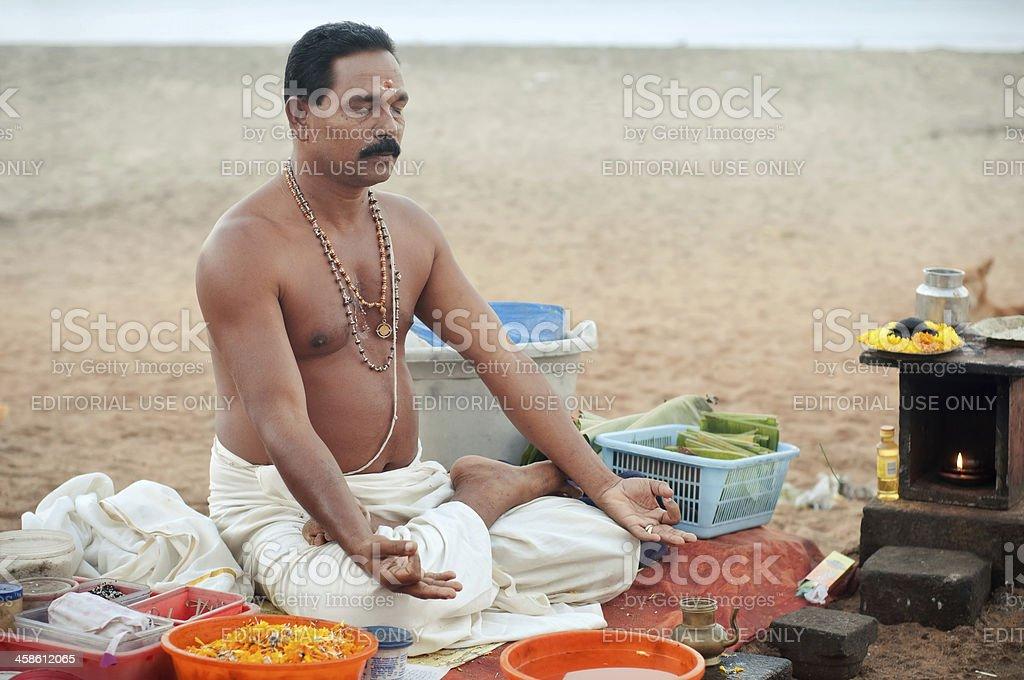 Hindu monk meditating on the beach. stock photo