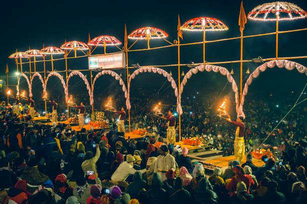 Hindu Pandits of Varanasi perform the Ganga Aarti ritual to worship holy river Ganga. Varanasi, Uttar Pradesh, India - December 26, 2019: A crowd of people gathers on the bank of river Ganga to take part in the Aarti ritual. Hindu Pandits of Varanasi perform the Ganga Aarti ritual every evening for one hour from 6 pm onward at Dashashwamedh Ghat. dashashwamedh ghat stock pictures, royalty-free photos & images