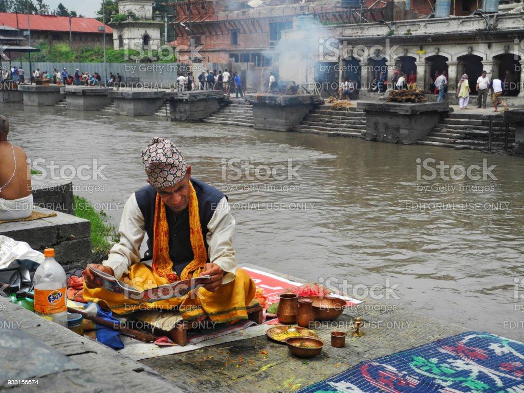 Hindu priest in religious clothing reading at Pashupatinath temple Kathmandu stock photo