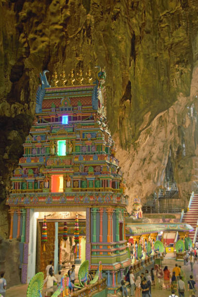 Hindu temple inside of the Batu caves. Malaysia, Kuala lumpur - december 30 ,2019. Land mark Batu caves:  Aerial view of the inside. Hindu temple. Looking through the limestone Cave. Left side is a colorful prayer. batu caves stock pictures, royalty-free photos & images