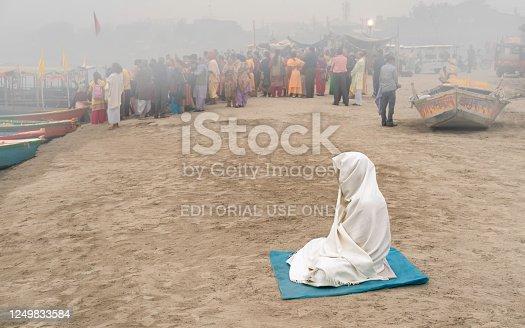 Vrindavan, Indian - November 14, 2019: Solitary Hindu woman covered in shawl deep in mediation on bank of river Jamuna at dawn on November 14, 2019 in Vrindavan, Uttar Pradesh, India.