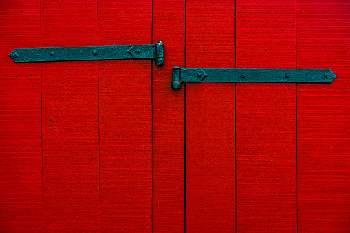 A set of metal hinges on old, red barn siding