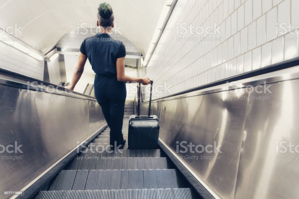 hip confident businesswoman traveling with suitcase stock photo
