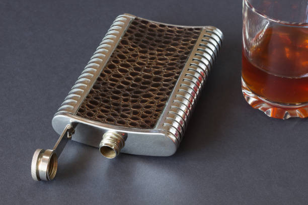 hip flask  and glass on a black background stock photo