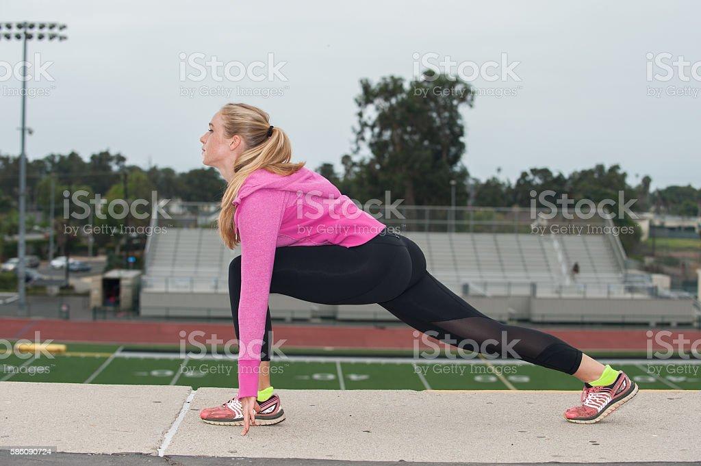 Hip flexor stretch over the field. stock photo