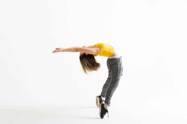 Hip Hop Dancer Doing Backbend While Standing On Tiptoes Side view of hip hop dancer doing backbend while standing on tiptoes over white background bending over backwards stock pictures, royalty-free photos & images