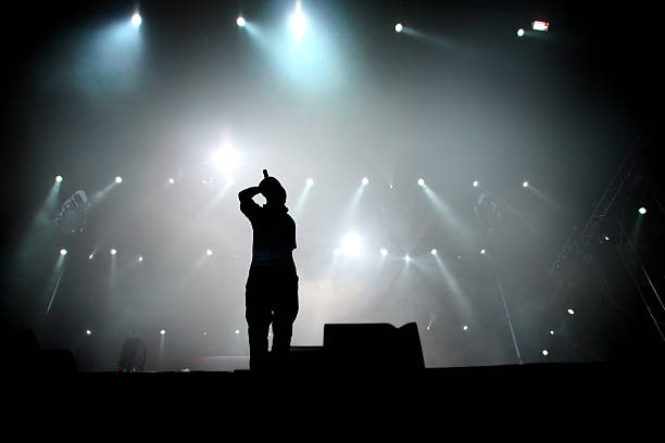 Hip hop singer Silhouette of hip hop singer on stage.  singer stock pictures, royalty-free photos & images