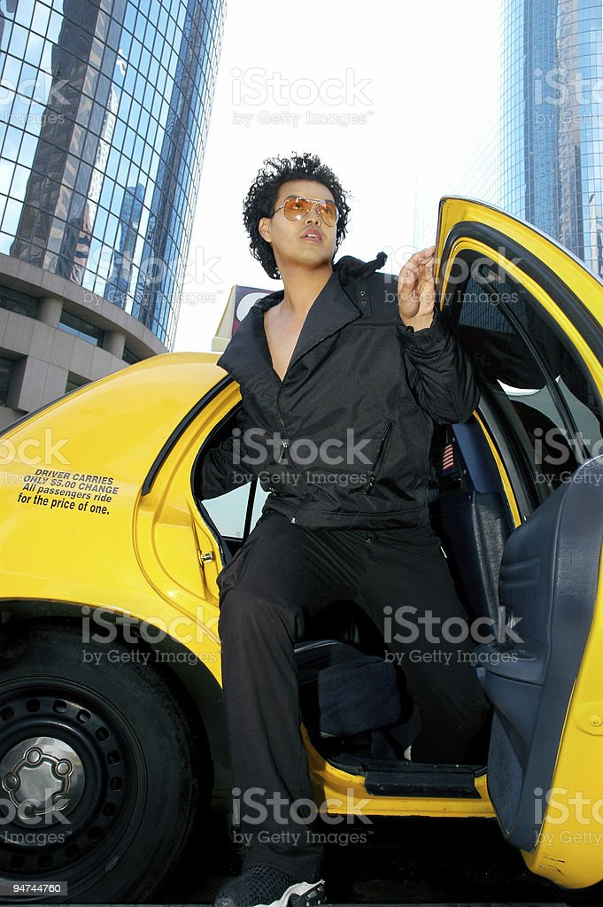 Hip Hop Young Man Exiting Taxi with Skyscrapers Behind royalty-free stock photo