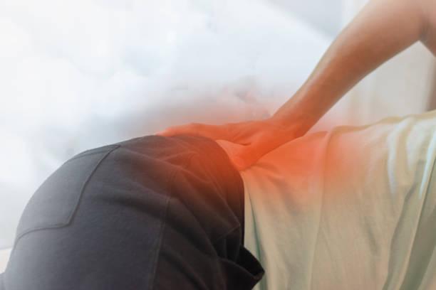 엉덩이 관절 통증 개념. 부상이나 관절염으로 고통으로 빨간 반점으로 그의 허리에 남자 손 - 엉덩관절 뉴스 사진 이미지