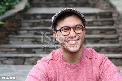 Hip man smiling wearing eyeglasses and hat.