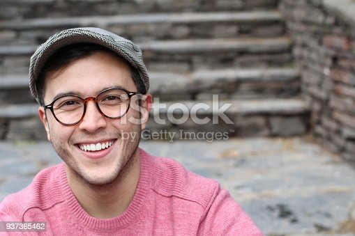 Hip man smiling wearing eyeglasses and hat.