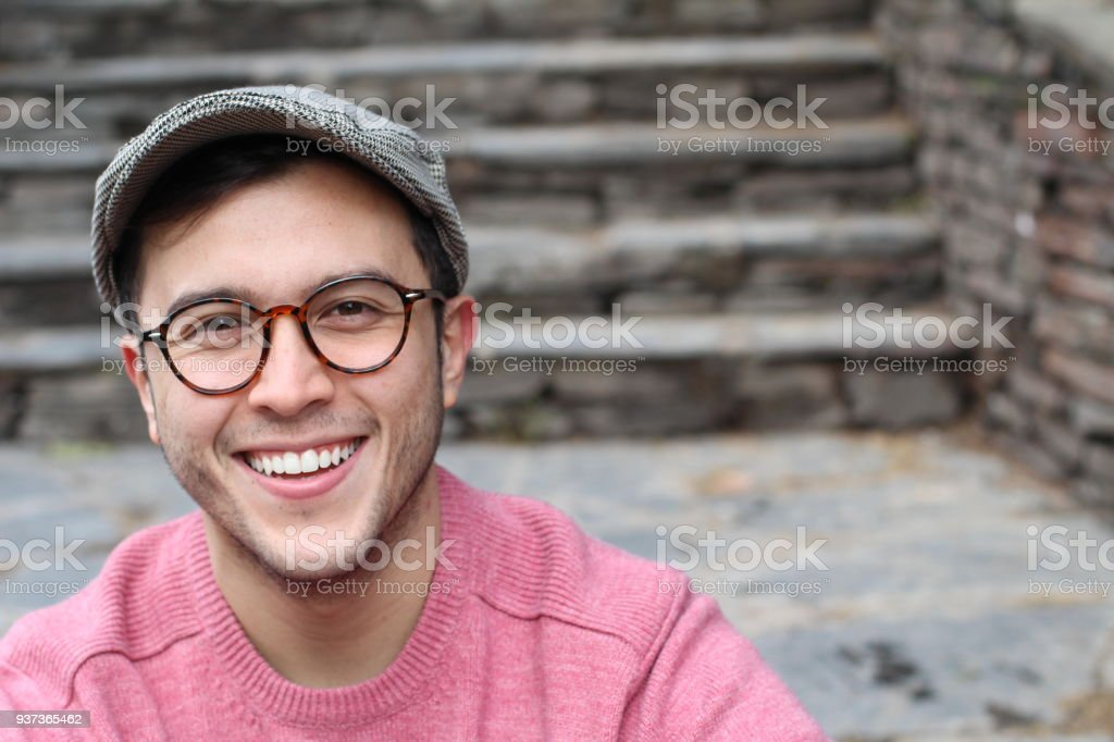 Hip man smiling wearing eyeglasses and hat stock photo