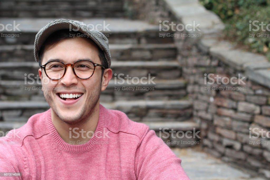 Hip man smiling wearing eyeglasses and hat stock photo