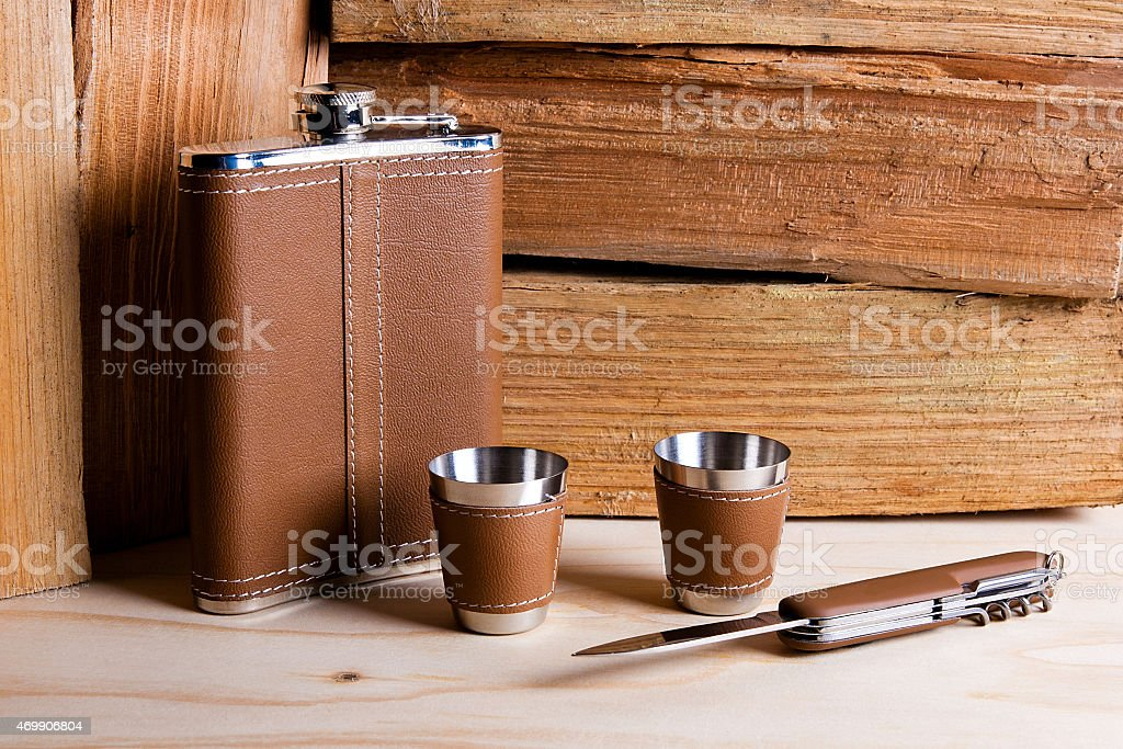 Hip metal flask, cups and knife on wooden background. stock photo