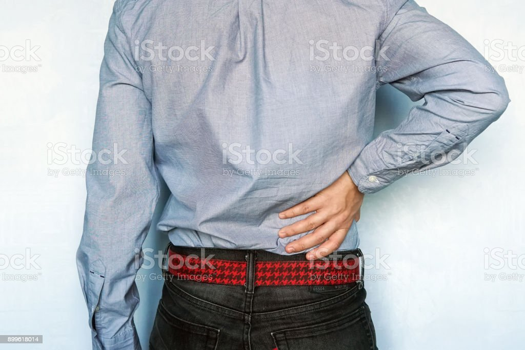 Hip or back injury. Young man touching his hurt right side of body. stock photo