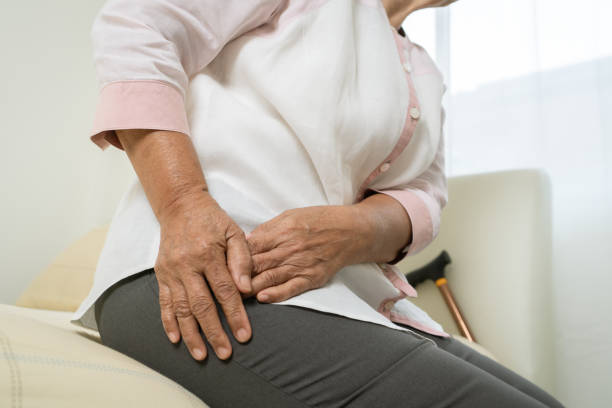 Hip pain of senior woman at home, healthcare problem of senior concept stock photo