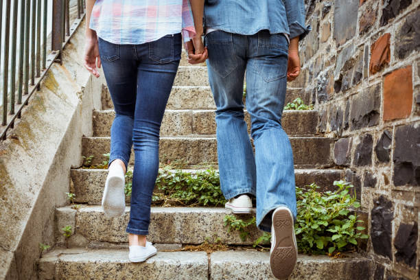 Hip young couple walking up steps Hip young couple walking up steps on a sunny day in the city skinny pants stock pictures, royalty-free photos & images