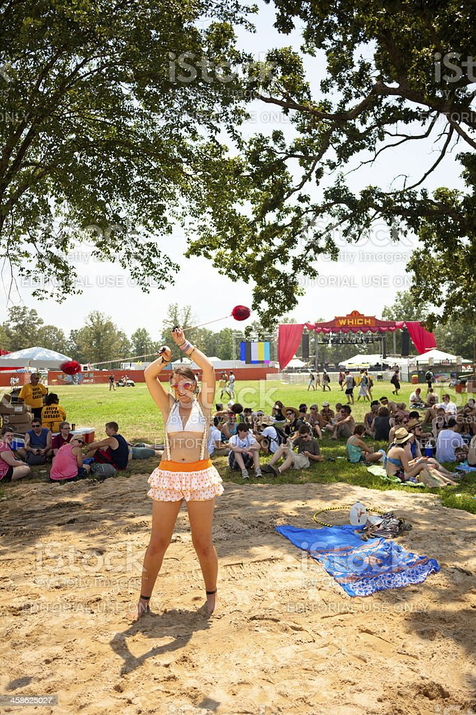 Hip young girl twirling (poi) balls at a music festival stock photo