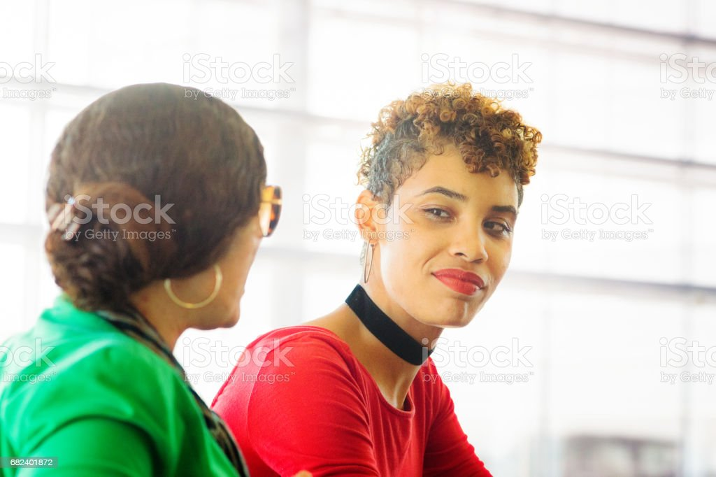 Hip young mixed race millennial female impressed by sales pitch royalty-free stock photo
