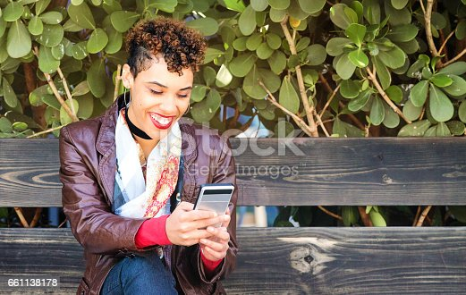 Hip young urban mixed race woman having fun social networking on mobile phone while waiting for friends on wooden bench.