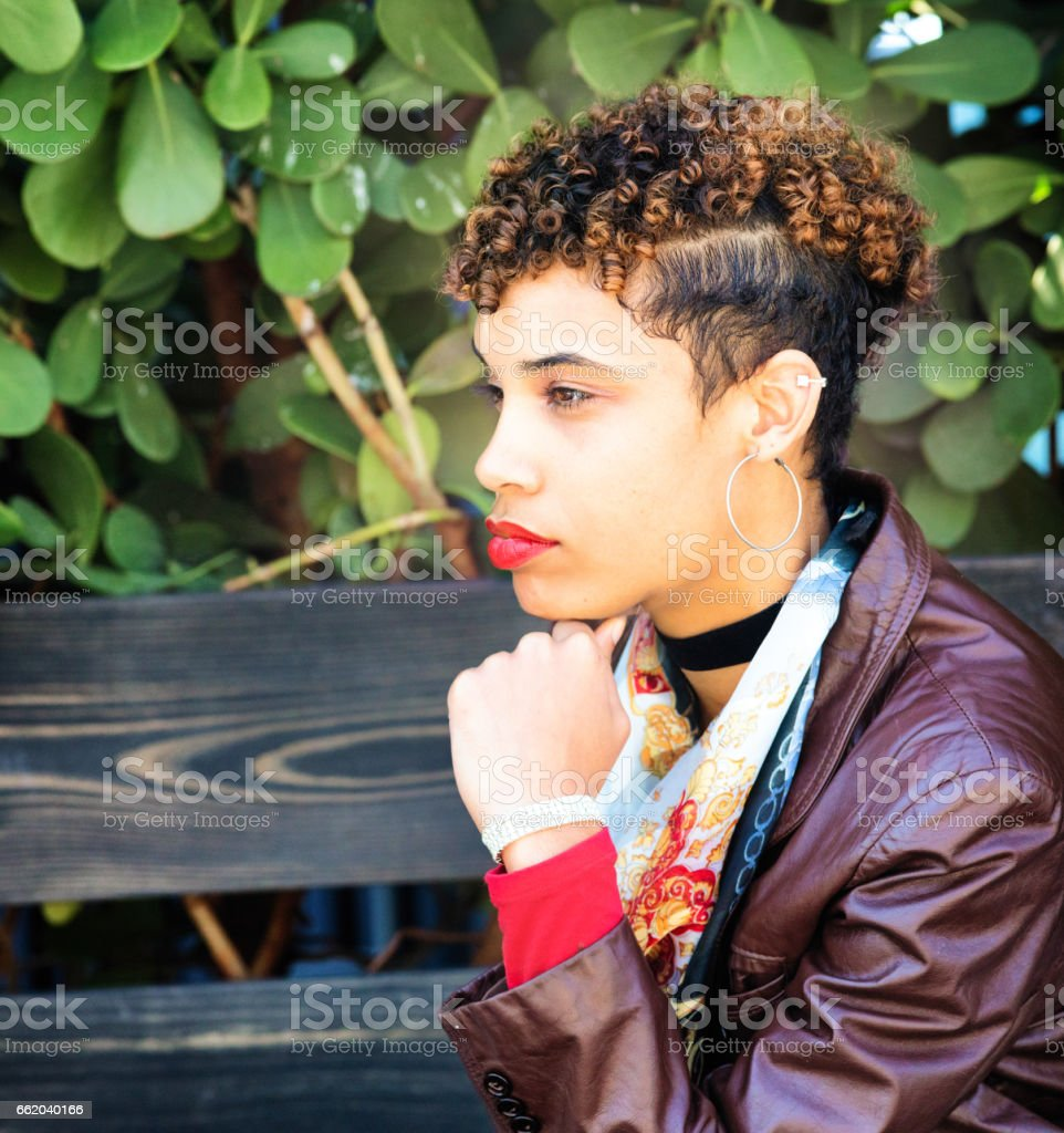 Hip young urban mixed race woman profile portrait on bench royalty-free stock photo