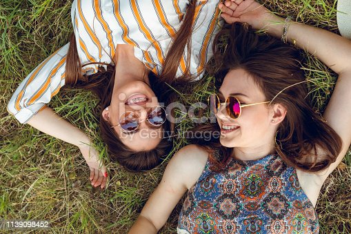 Two young women are lying down on grass in a park