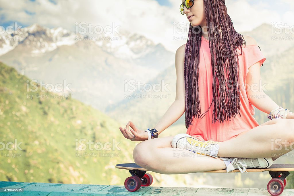 hippie fashion girl doing yoga, relaxing on skateboard at mountain stock photo